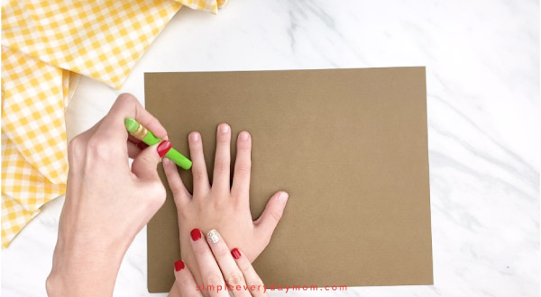 adult hands tracing childs hand on brown paper