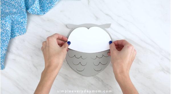 Hands gluing owl face onto craft