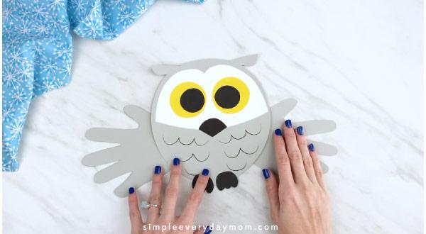 Hands gluing handprint wings onto owl craft