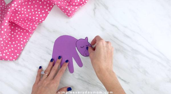 Hands gluing unicorn head to handprint body