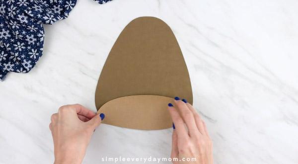 Hands gluing light brown paper to dark brown walrus body