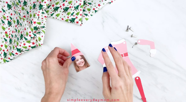 Hands gluing elf hat to girl photo