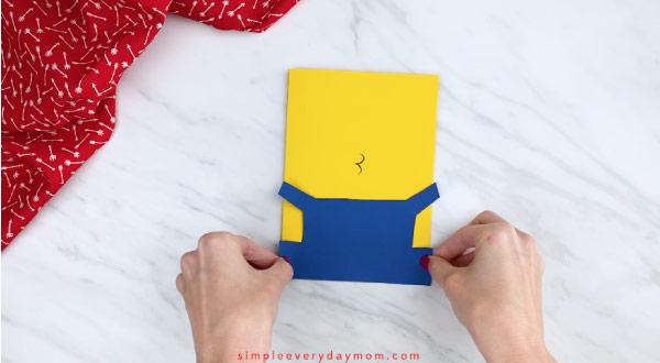 Hands gluing minion overalls onto minion card