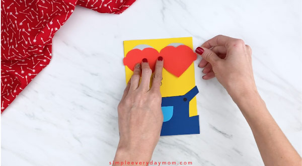 Hands gluing heart sunglasses onto minion card