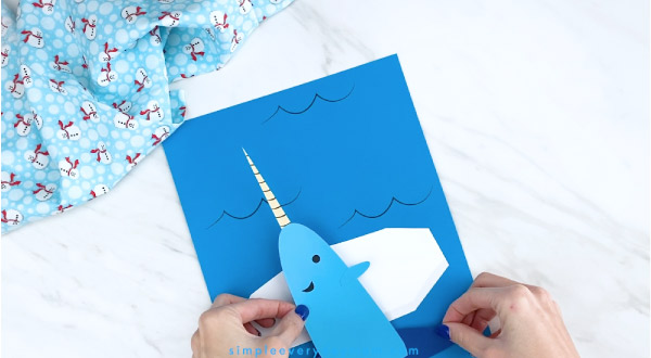 Hands gluing narwhale to blue paper