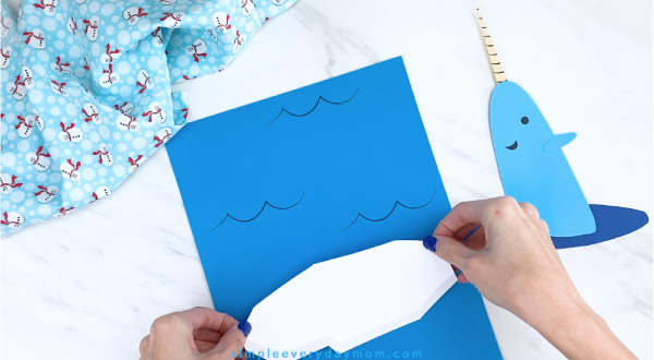 Hands gluing paper iceberg to blue paper