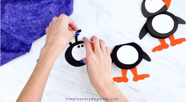 Hands gluing puffin antenna to head
