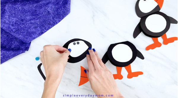 Hands gluing puffin face to head