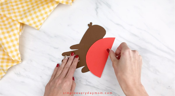hands gluing red paper to handprint robin craft