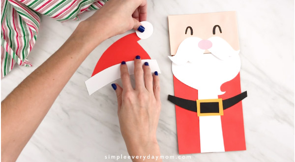 Hands gluing Pom to Santa hat
