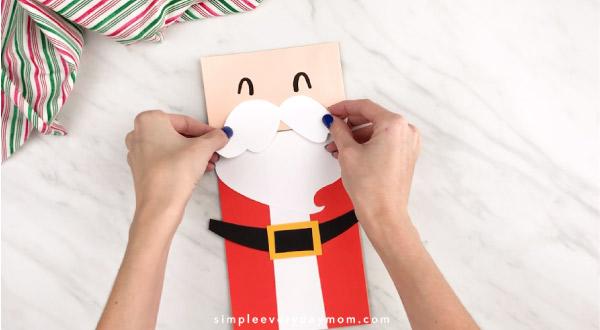 Hands gluing Santa mustache to face