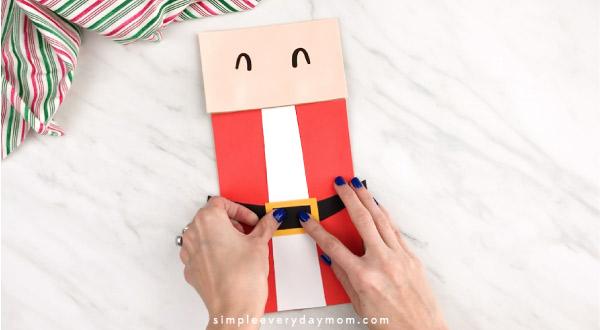 Hands gluing buckle inside onto paper bag Santa