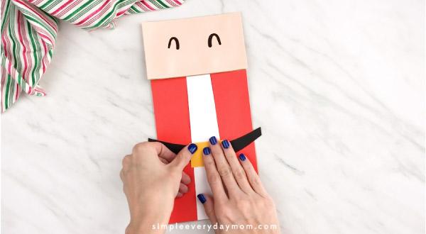 Hands gluing belt buckle onto paper bag Santa craft