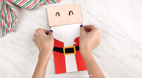 Hands gluing Santa beard onto paper bag craft