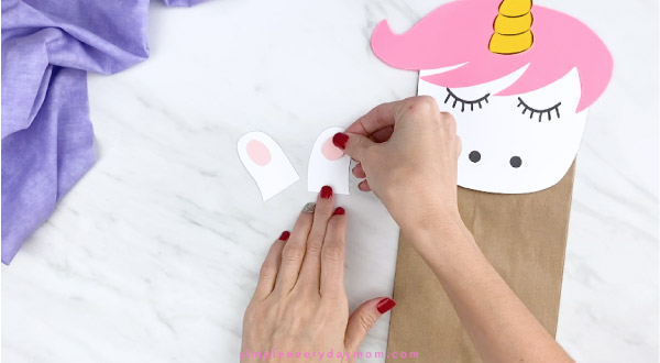 hands gluing inner ears to paper unicorn craft