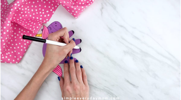 Hands drawing hooves onto handprint unicorn