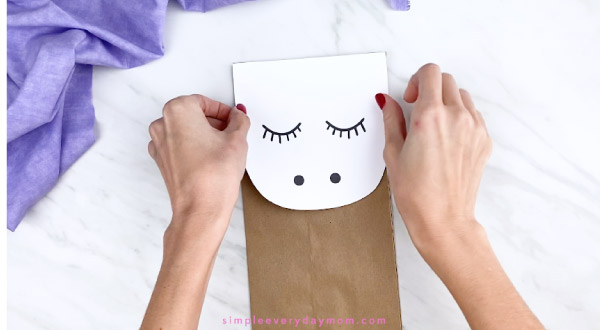hands gluing unicorn face onto brown paper bag