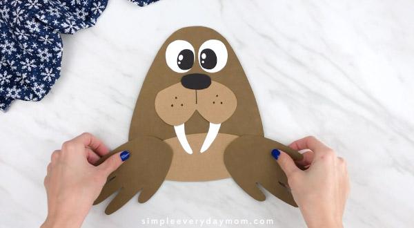 Hands gluing handprint flippers to walrus craft