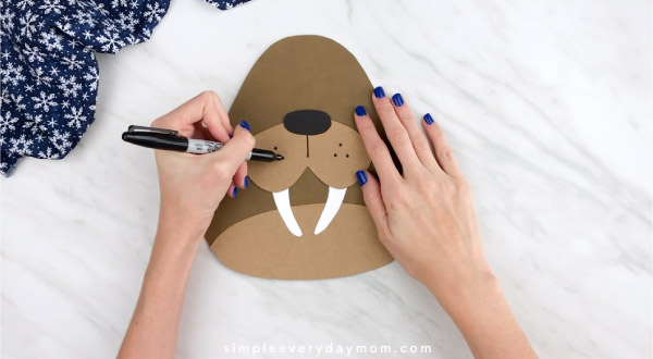 Hands drawing walrus whisker holes on craft