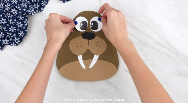 Hands gluing eyes to walrus craft
