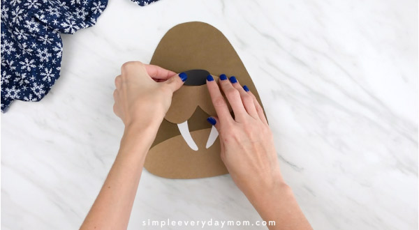 Hands gluing nose to walrus craft