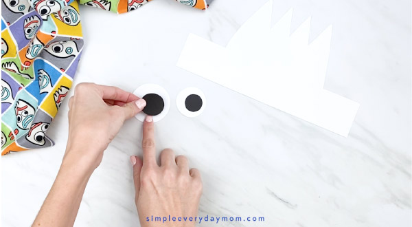 hands gluing paper pupil onto eye