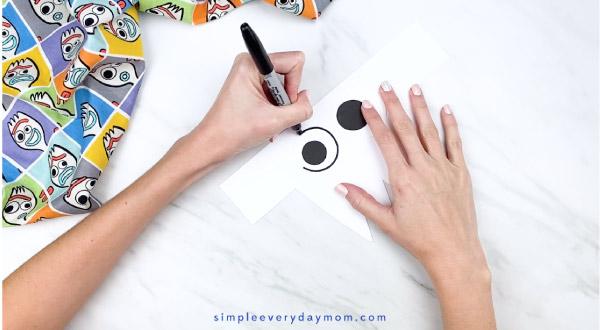 hands outline paper eye with black marker