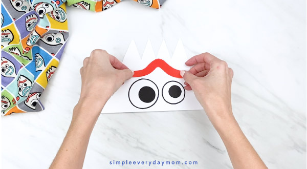 hands gluing paper Forky eyebrow onto headband