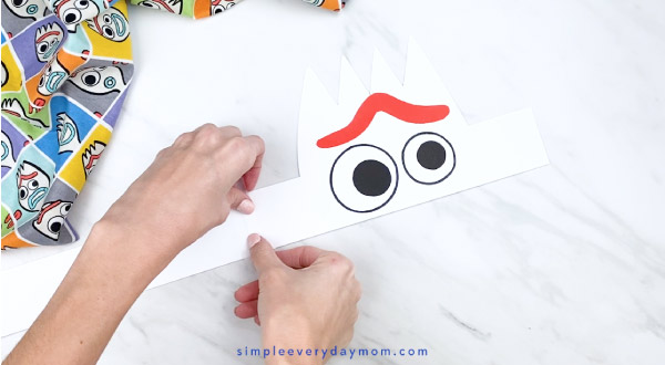 hands taping on headband extender onto Forky paper headband