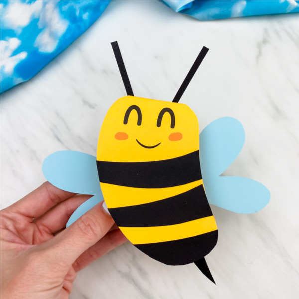 Hand holding paper bee card craft