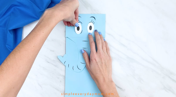 Hands gluing eyes to Horton puppet craft