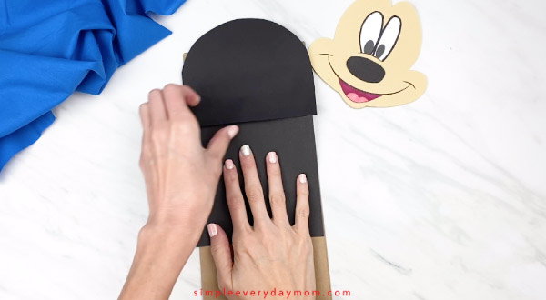 hands gluing mickey mouse body onto paper bag