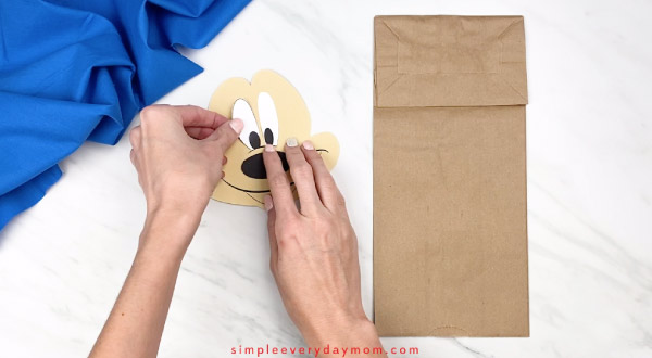 hands gluing eyes onto mickey mouse paper craft