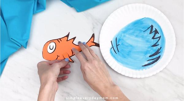Hands gluing fish fin onto Dr. Seuss craft