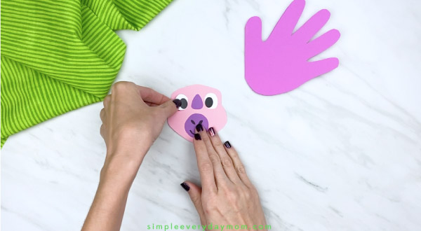 hands gluing eyes onto paper dinosaur craft