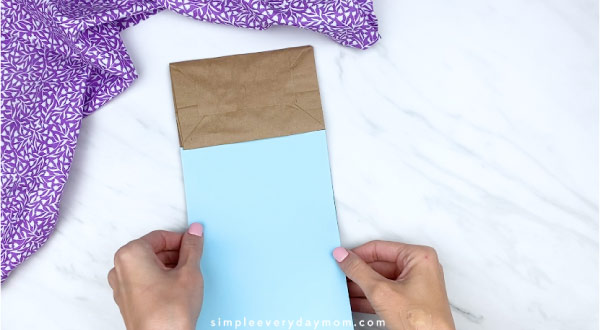 Hands gluing blue paper onto brown paper bag