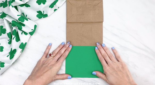 Hands gluing green paper onto brown paper bag