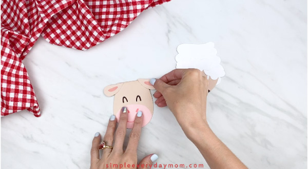 Hands gluing ears onto paper sheep card craft