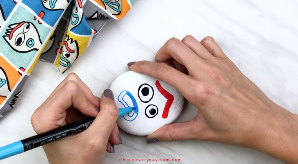 hands coloring in Forky\'s mouth with blue paint pen