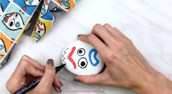 hands drawing on forky prong onto Forky painted rock