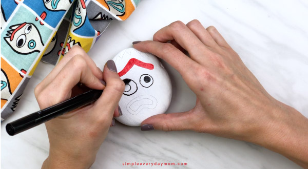 hands coloring in Forky\'s eyes on painted rock