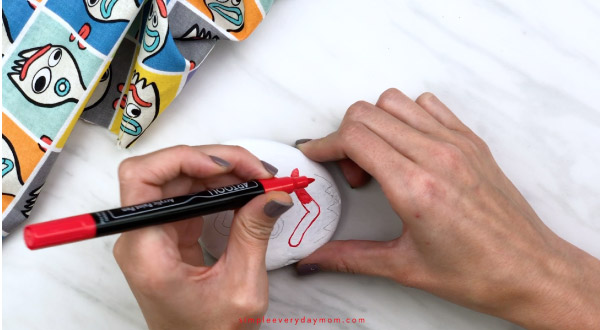 hands coloring in Forky\'s eyebrow with red paint pen
