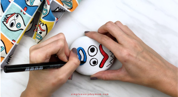 hands outlining Forky\'s mouth with black paint pen