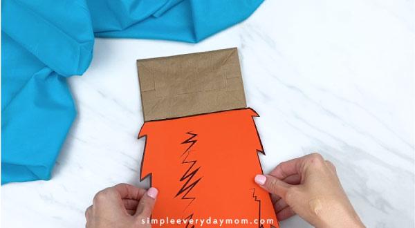 Hands gluing fox in socks body to paper bag