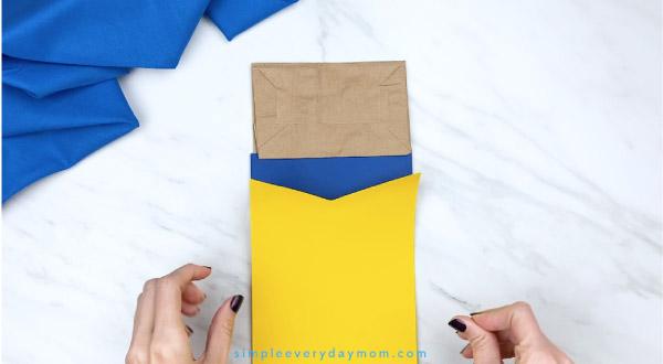 hands gluing shirt onto Pete the Cat paper bag craft