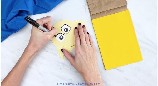 Hands outlining Sam I Am eyes with black marker