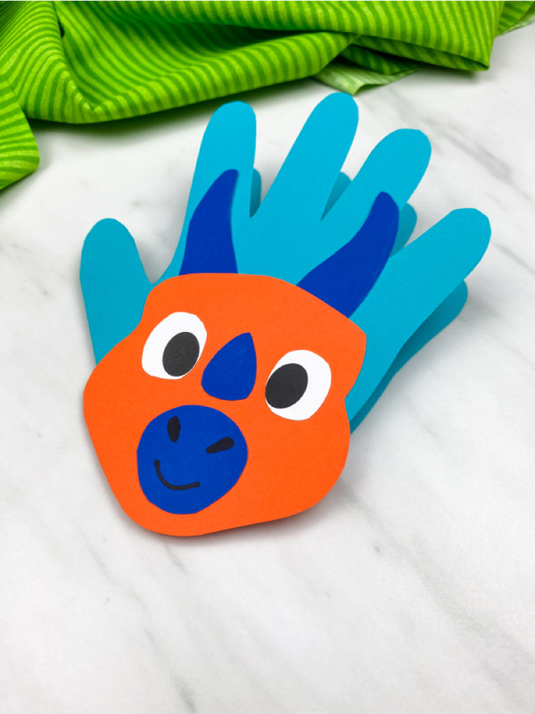 closeup of orange/blue handprint dinosaur card
