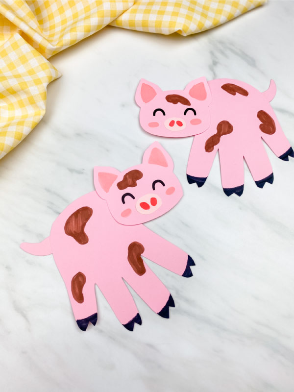 Two handprint pig crafts