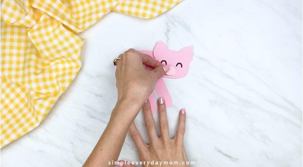 Hands gluing nose onto handprint pig craft