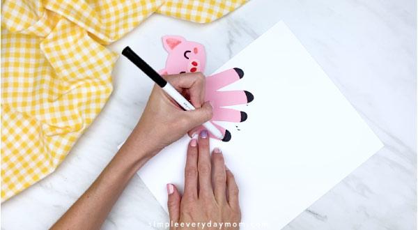 Hands drawing hooves onto handprint pig